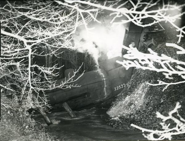 Steam engine in stream after small bridge had collapsed on the Midhurst to Chichester line, 19th November 1951. Photographed by George Garland. George Garland Collection. West Sussex Record Office Ref No: Garland N36924