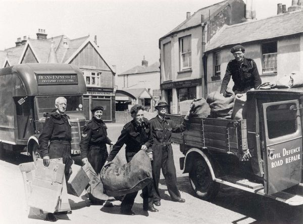 [1939-1945]. The men are collecting paper and cardboard from West Street and loading it into a pick-up (the van door is signed 'Civil Defence Road Repair'). Another van has 'Beans Express Ltd Transport Contractors' on the front