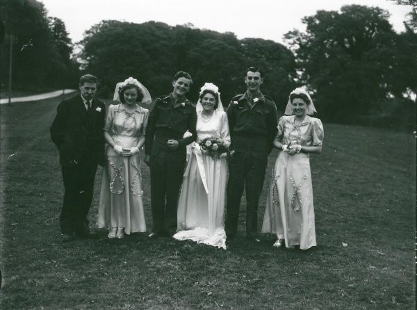 Wedding party posing in church grounds at Ebernoe, Sussex, Groom and Best Man in army uniform. 10 May 1947 George Garland collection West Sussex Record Office Ref No: Garland N28045